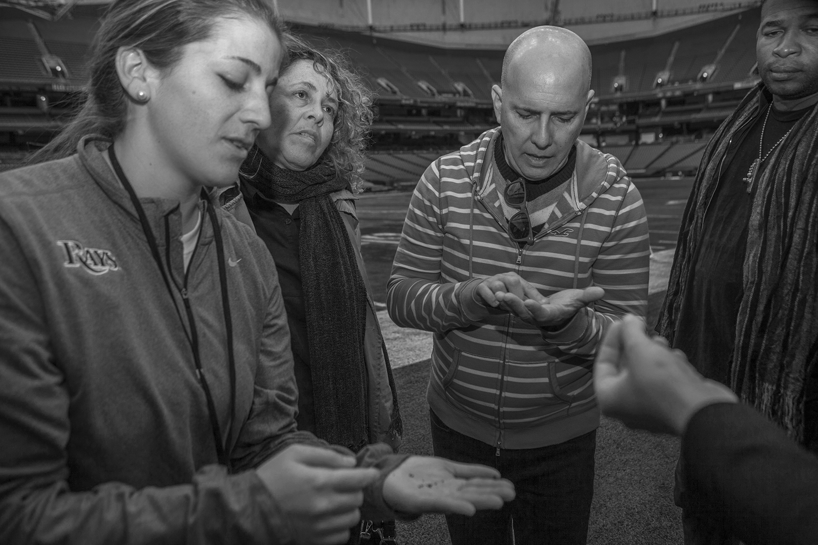 Tropicana Field Senior Event Coordinator Kelsey Smith (L) explains the Tropicana''s field composition to members of the visiting Cuba arts delegation.