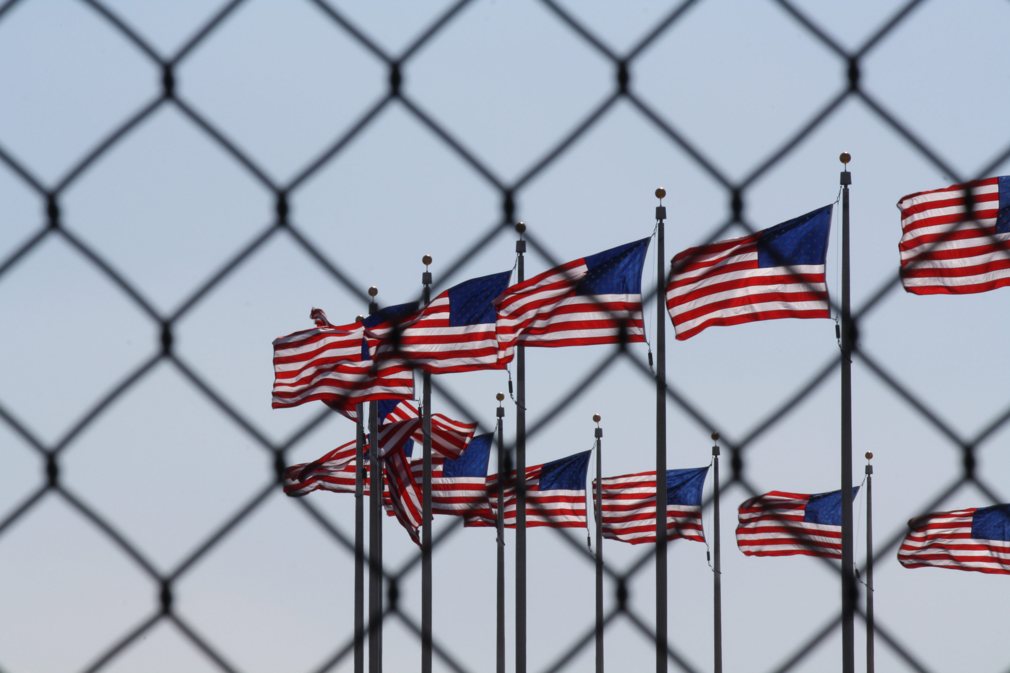 us-flags-behind-fence-prison-3500x2333.jpeg