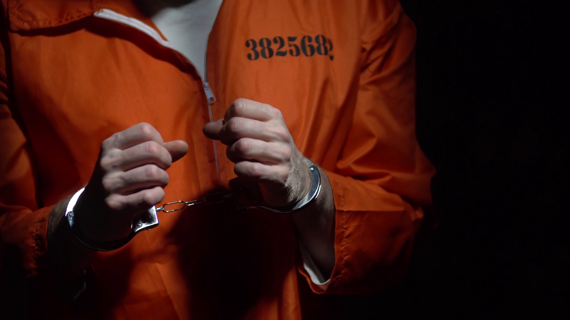 videoblocks-prison-convict-in-handcuffs-dark-at-night-in-cell-behind-bars-sad-depressing-alone-solitary-confinement-male-adult-prisoner-wearing-orange-jumpsuit-young-offender-serving-time-tr