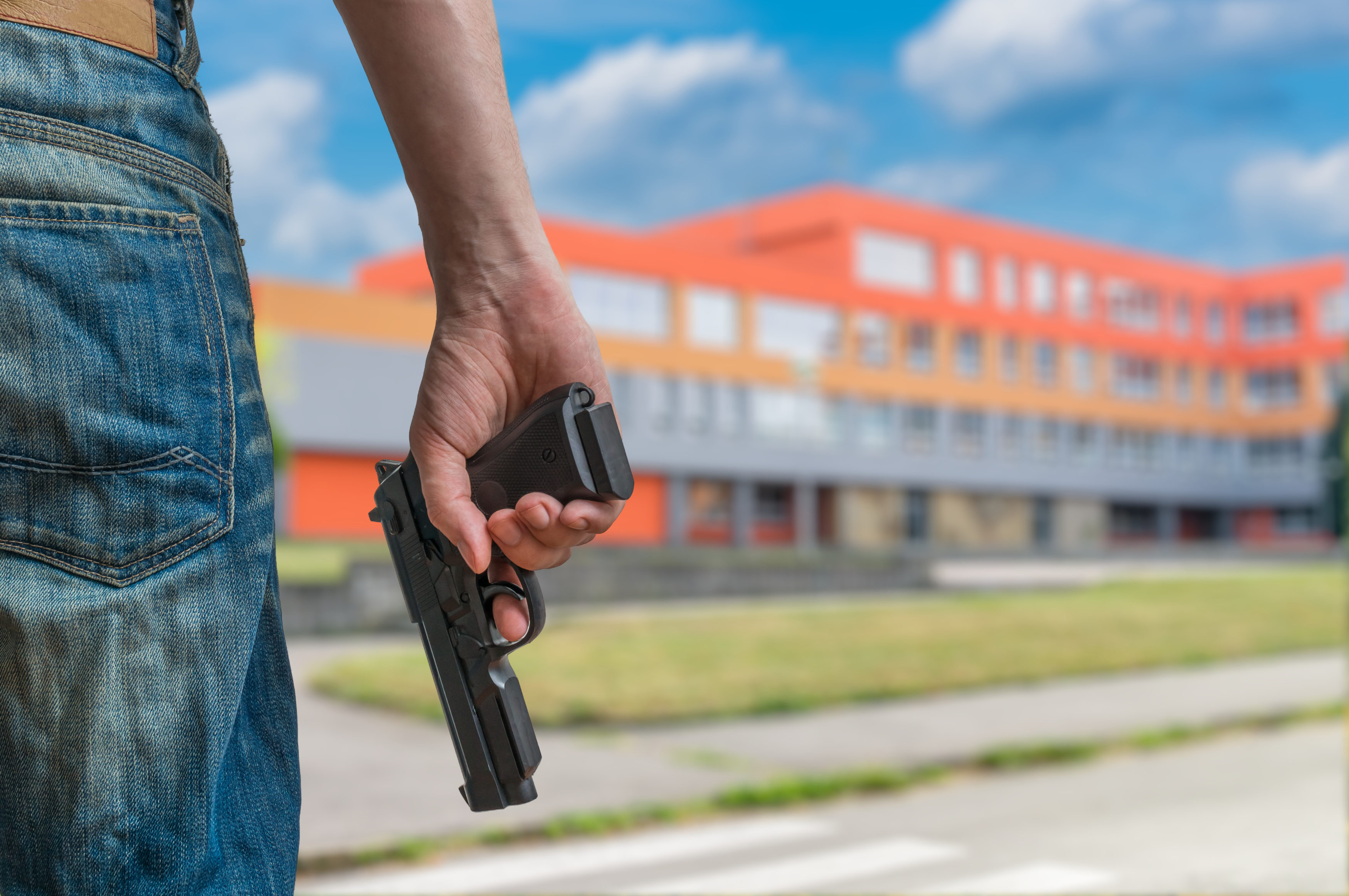Gun control concept. Young armed man holds pistol in hand in public place near high school.