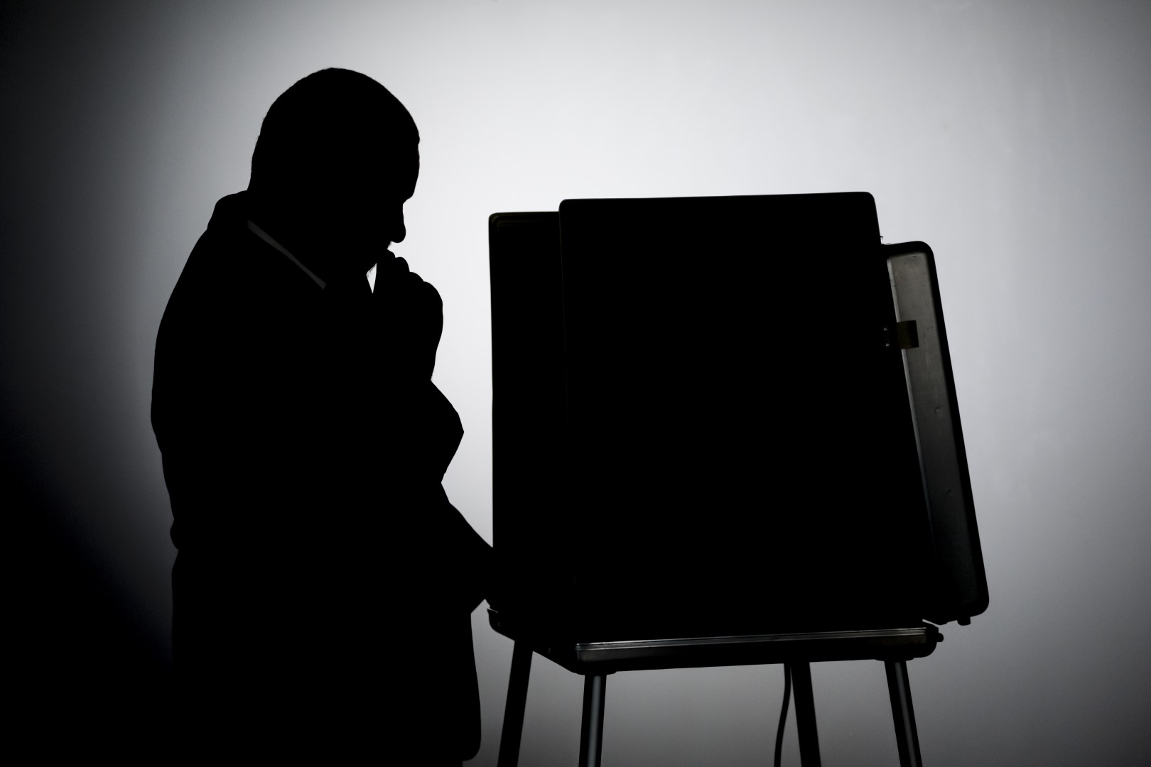 Man voting in a voting booth, silhouette shot