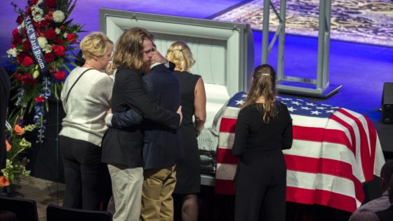 Dustin Walters, center left, hugs his brother Mason Walter, center right, during a funeral service for their brother and U.S. Navy Airmen Apprentice, Cameron Walters, at the Compassion Christian Church in Savannah, Ga., Monday, Dec. 16, 2019. Cameron Walters was one of the three Navy sailors killed in a Saudi gunman's attack at Naval Air Station Pensacola in Florida on Dec. 6. (Stephen B. Morton/Atlanta Journal-Constitution via AP)