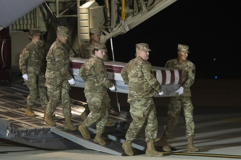 An Air Force carry team moves a transfer case containing the remains of Navy Ensign Joshua Watson on Sunday, Dec. 8, 2019, at Dover Air Force Base, Del. A Saudi gunman killed three people including 23-year-old Watson, a recent graduate of the U.S. Naval Academy from Enterprise, Ala., in a shooting at Naval Air Station Pensacola in Florida. (AP Photo/Cliff Owen)