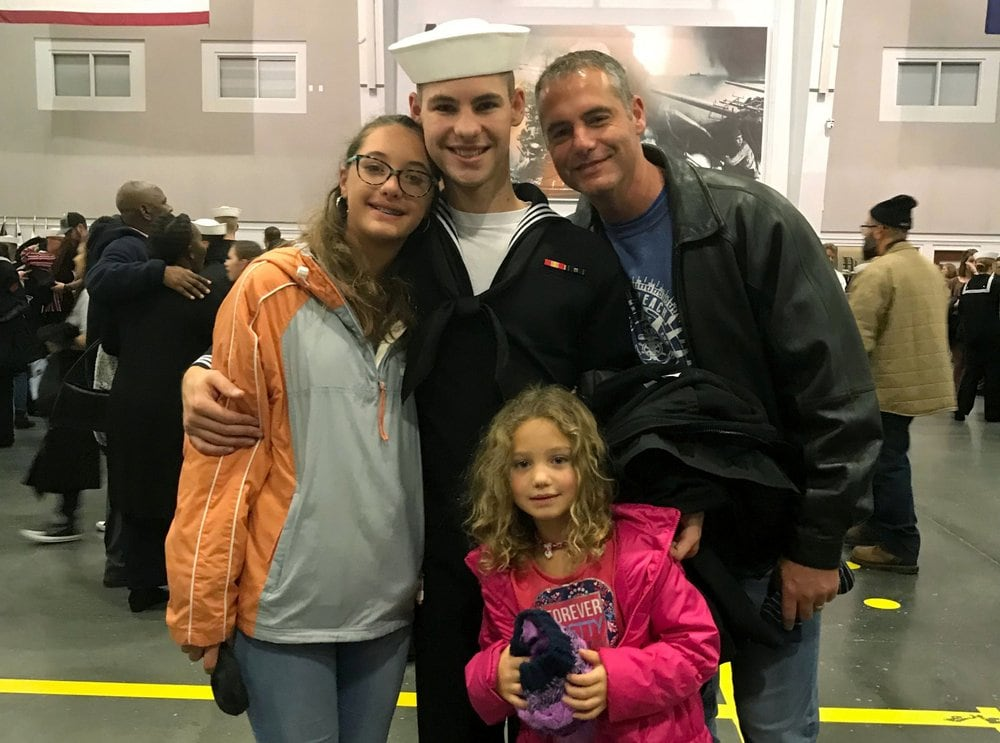 In this Nov. 22, 2019 photo provided by the Walters Family, Cameron Walters, center in Navy uniform, poses for a photo with his sisters, Lily Walters, left, and Shania Walters, right, and his father, Shane Walters, far right, the day he graduated from boot camp in Great Lakes, Ill. Cameron Walters, 21, of Richmond Hill, Georgia, was among three sailors killed at Naval Air Station Pensacola in Florida on Friday, Dec. 6. (Heather Walters/Courtesy of the Walters Family via AP)