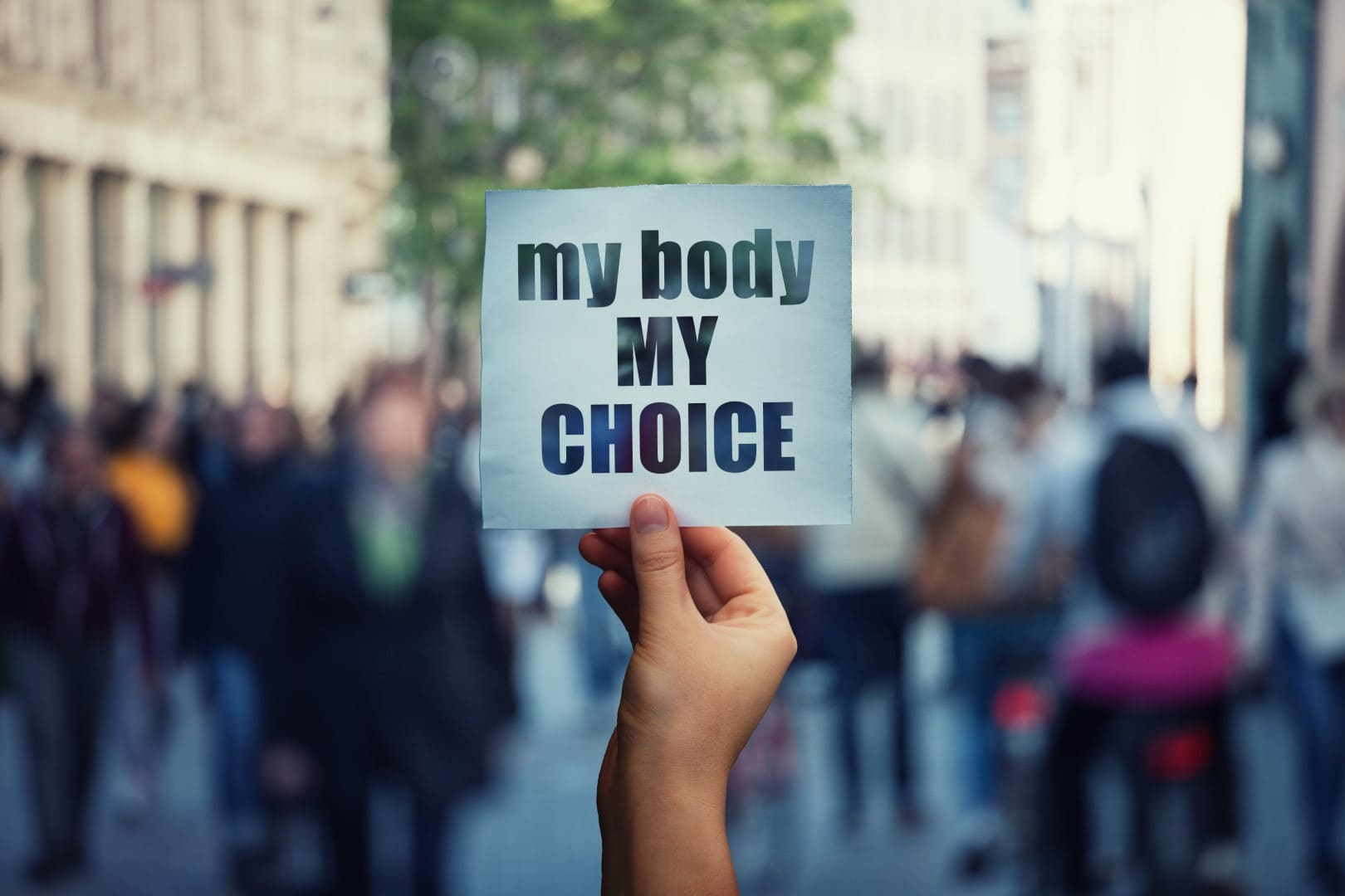 Feminist hands holding a protest banner with the message my body my choice over a crowded street. Human rights concept against fetus law and reproductive justice. Stop discrimination and injustice