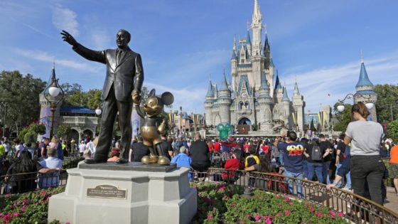 FILE - In this Jan. 9, 2019 photo, guests watch a show near a statue of Walt Disney and Micky Mouse in front of the Cinderella Castle at the Magic Kingdom at Walt Disney World in Lake Buena Vista, Fla. Disney officials said Monday, Feb. 17, 2020, that the iconic Cinderella Castle would be renovated over the next several months. The most noticeable changes will be the addition of gold trim to most of the castle and the darkening of the blue hue on the castle's turrets. Work on the castle will last through the summer. (AP Photo/John Raoux, File)