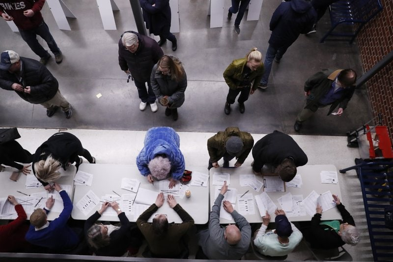 Caucus goers check in at a caucus at Roosevelt Hight School, Monday, Feb. 3, 2020, in Des Moines, Iowa. (AP Photo/Andrew Harnik)