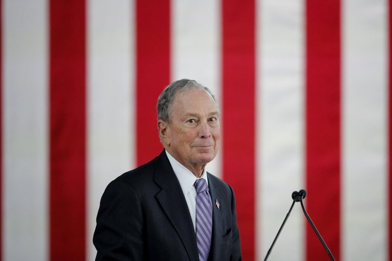 bloomberg, mike - in front of a red flag