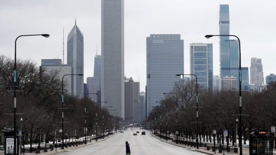 """An elderly lady walks across the usually busy Columbus Drive that splits Chicago's Grant Park in half, on the first work day since Illinois Gov. J.B. Pritzker gave a shelter in place order last week, Monday, March 23, 2020, photo, in Chicago. Gov. J.B. Pritzker says Illinois is not receiving enough medical supplies in its fight against the coronavirus. Pritzker tells CNN's """"State of The Union"""" that Illinois got a recent supply but it was a fraction of what was requested from the federal government. The comments prompted angry tweets from President Donald Trump who says governors should not be """"blaming the federal government for their own shortcomings.""""(AP Photo/Charles Rex Arbogast)"""
