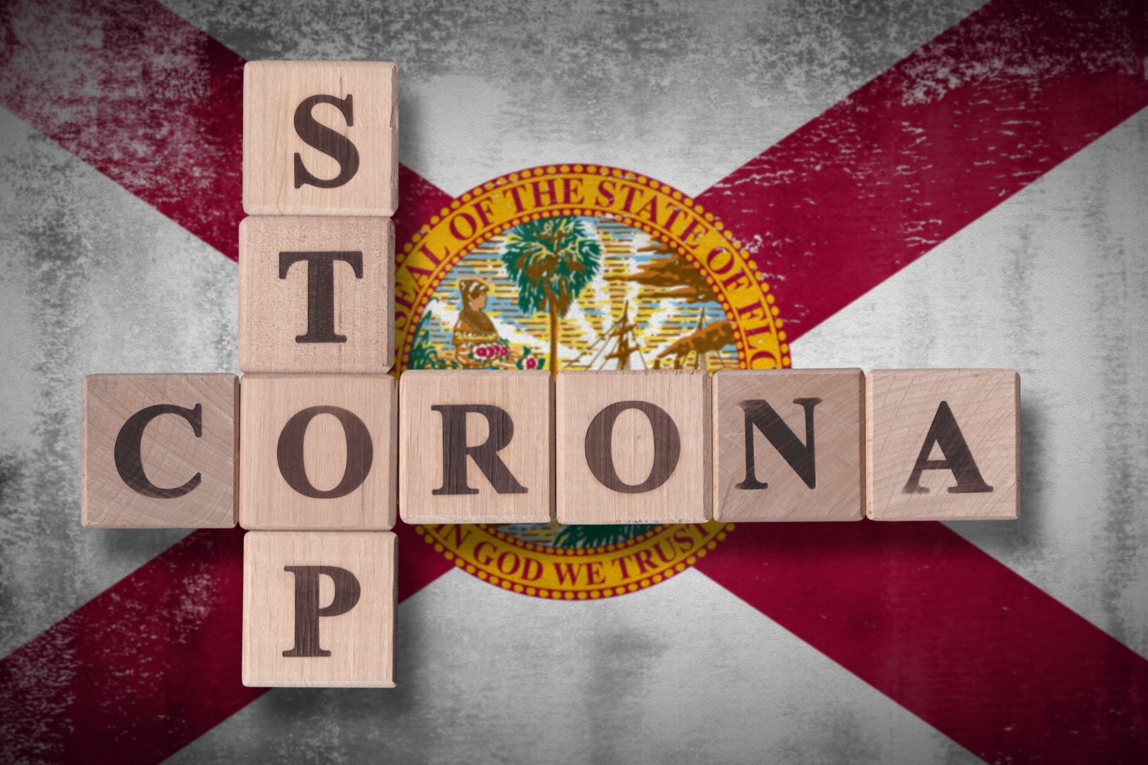 Flag of the state of Florida with wooden cubes spelling STOP CORONA on it. 2019 - 2020 Novel Coronavirus (2019-nCoV) concept art, for an outbreak occurs in Florida, US.