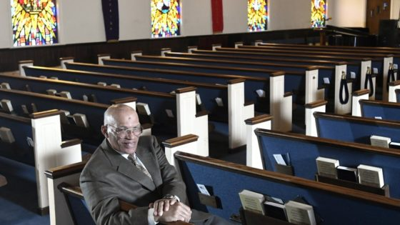 """The Rev. Alvin J. Gwynn Sr., of Friendship Baptist Church in Baltimore, sits in his church's sanctuary, Thursday, March 19, 2020. He bucked the cancellation trend by holding services the previous Sunday. But attendance was down by about 50%, and Gwynn said the day's offering netted about $5,000 compared to a normal intake of about $15,000. """"It cuts into our ministry,"""" he said. """"If this keeps up, we can't fund all our outreach to help other people."""" (AP Photo/Steve Ruark)"""