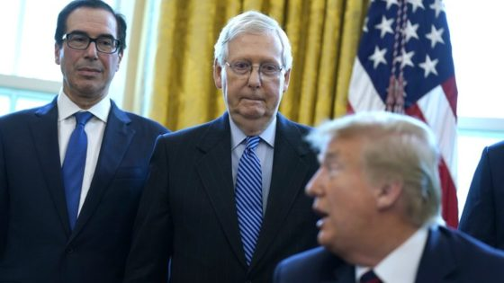 Treasury Secretary Steven Mnuchin and Senate Majority Leader Mitch McConnell, R-Ky., listen as President Donald Trump speaks before he signs the coronavirus stimulus relief package in the Oval Office at the White House, Friday, March 27, 2020, in Washington. (AP Photo/Evan Vucci)