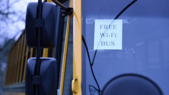 In this Thursday, March 26, 2020, photo, this wi-fi-enabled school bus, seen at an apartment complex in Winnsboro, S.C., is one of many being sent to rural and lower-income areas around South Carolina to help students with distance learning during the new coronavirus outbreak. With routers mounted inside, the buses broadcast enough bandwidth in an area the size of a small parking for parents to drive up and children to access the internet from inside their cars. (AP Photo/Meg Kinnard)