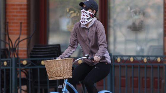 A bicyclist wears face protection against the new coronavirus while pedaling through Larimer Square early Saturday, April 25, 2020, in downtown Denver. (AP Photo/David Zalubowski)