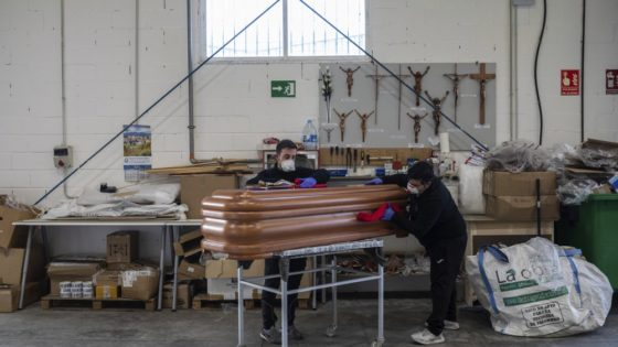 Two employees of CHAO coffins work at the company warehouse in Valdemoro, outskirts of Madrid, Spain, Friday, April 3, 2020. The new coronavirus causes mild or moderate symptoms for most people, but for some, especially older adults and people with existing health problems, it can cause more severe illness or death. (AP Photo/Bernat Armangue)