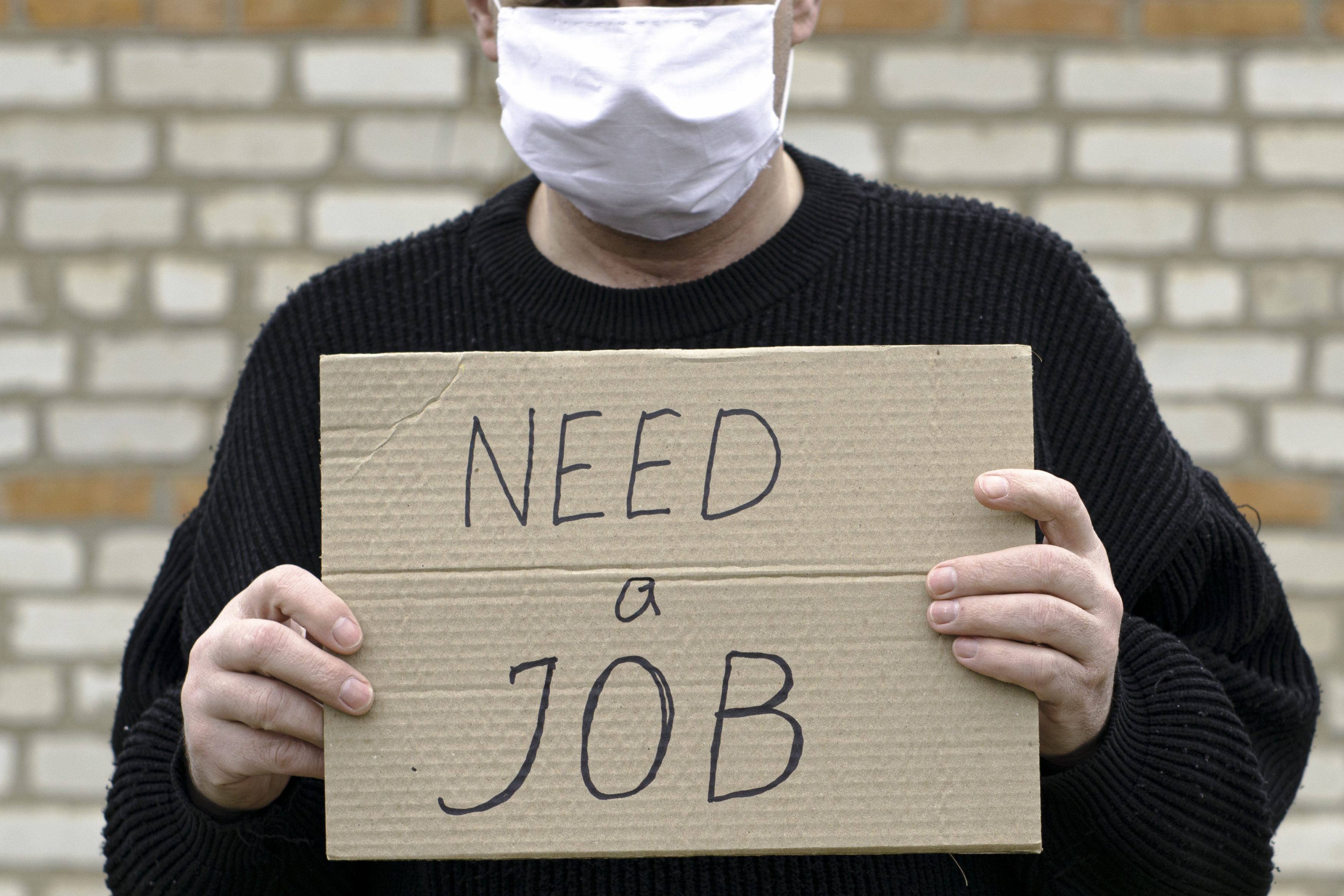 concept unemployment and coronavirus a man in a medical hygienic mask is holding a cardboard tablet with a inscription need a job
