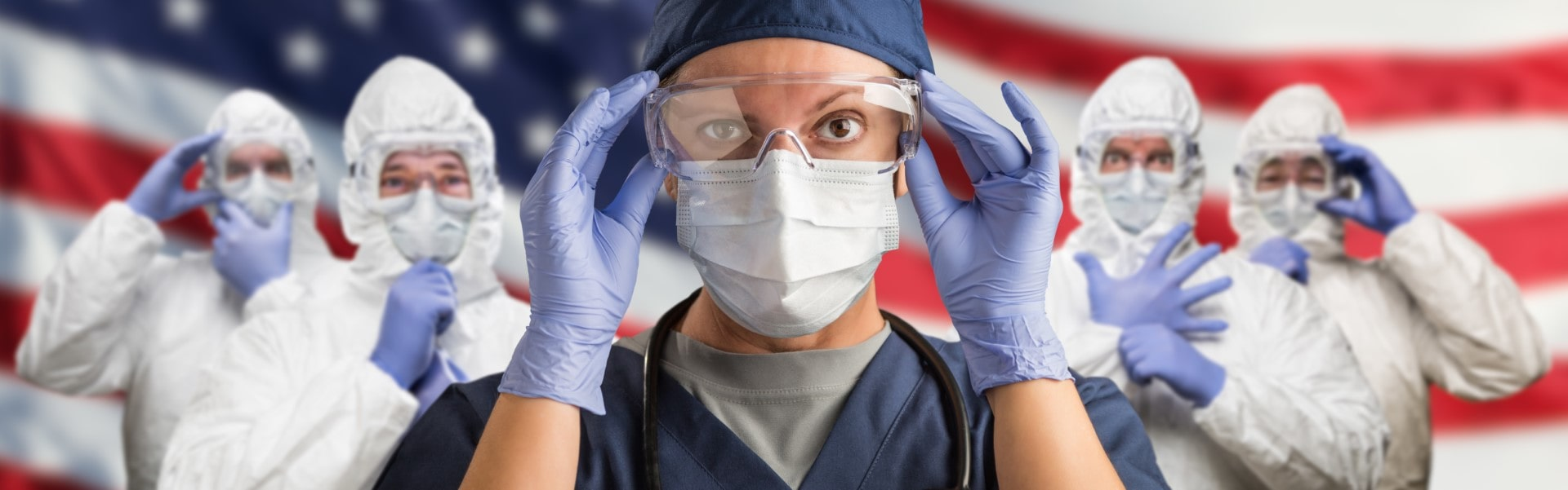 Doctors or Nurses Wearing Medical Personal Protective Equipment (PPE) Against The American Flag Banner.