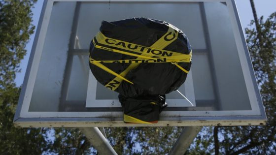 Yellow caution tape and a plastic tarp cover a basketball rim at McKinley Park in Sacramento, Calif., Tuesday, April 21, 2020. The park remains open but the rims were covered because people were not following social distancing rules in place due to the coronavirus outbreak. (AP Photo/Rich Pedroncelli)