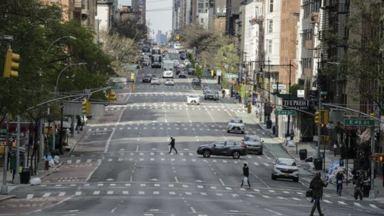 Pedestrians cross second avenue Thursday, April 16, 2020, in New York. New York planned for a long fight against the coronavirus outbreak amid hopeful hospitalization trends. Gov. Andrew Cuomo extended stay-at-home restrictions Thursday through mid-May and New York City is getting ready to use 11,000 empty hotel rooms for coronavirus quarantines. (AP Photo/Frank Franklin II)