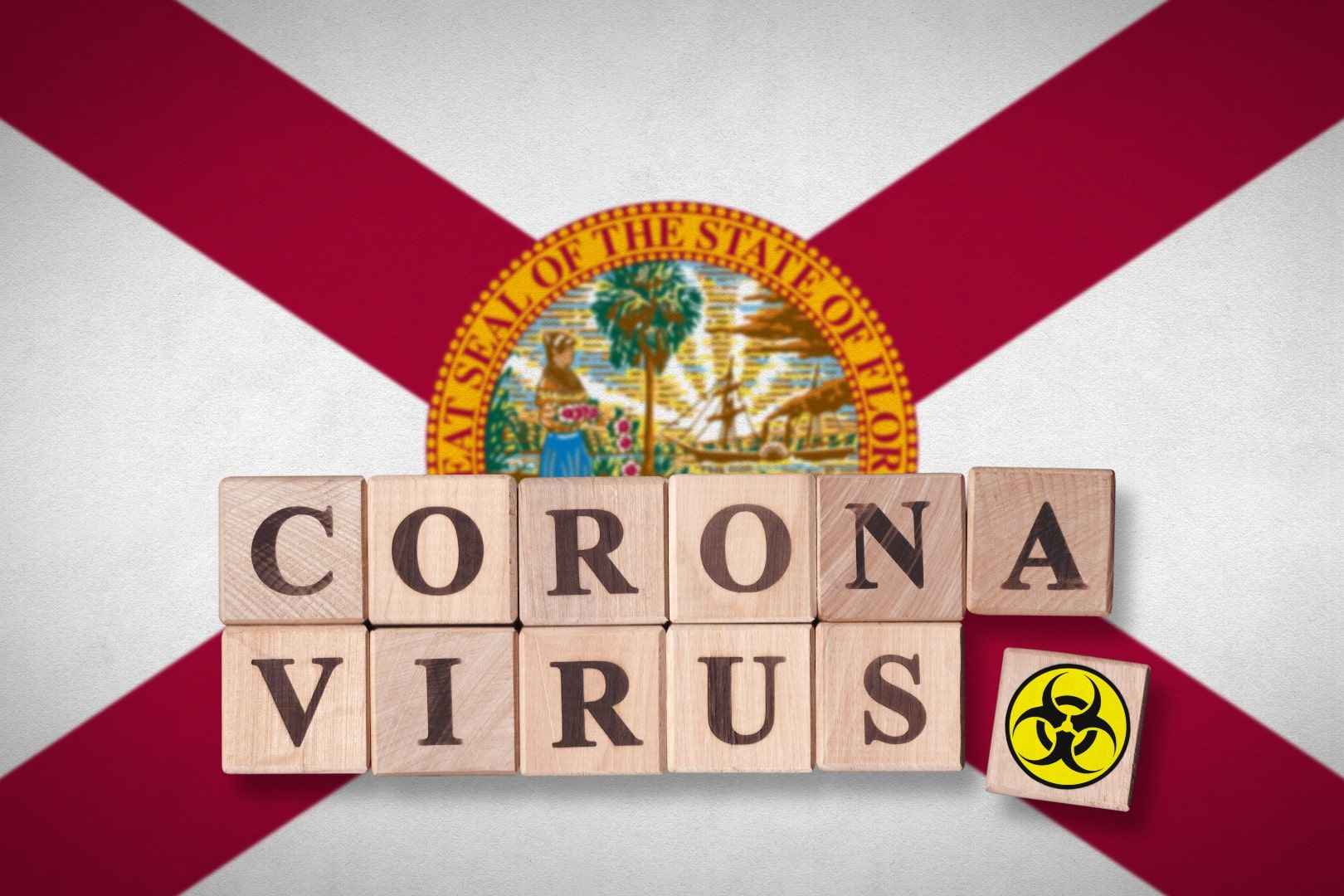 The state of Florida flag and wooden blocks with letters spelling CORONAVIRUS and quarantine symbol on it. Novel Coronavirus (2019-nCoV) concept for an outbreak occurs in Florida, US.