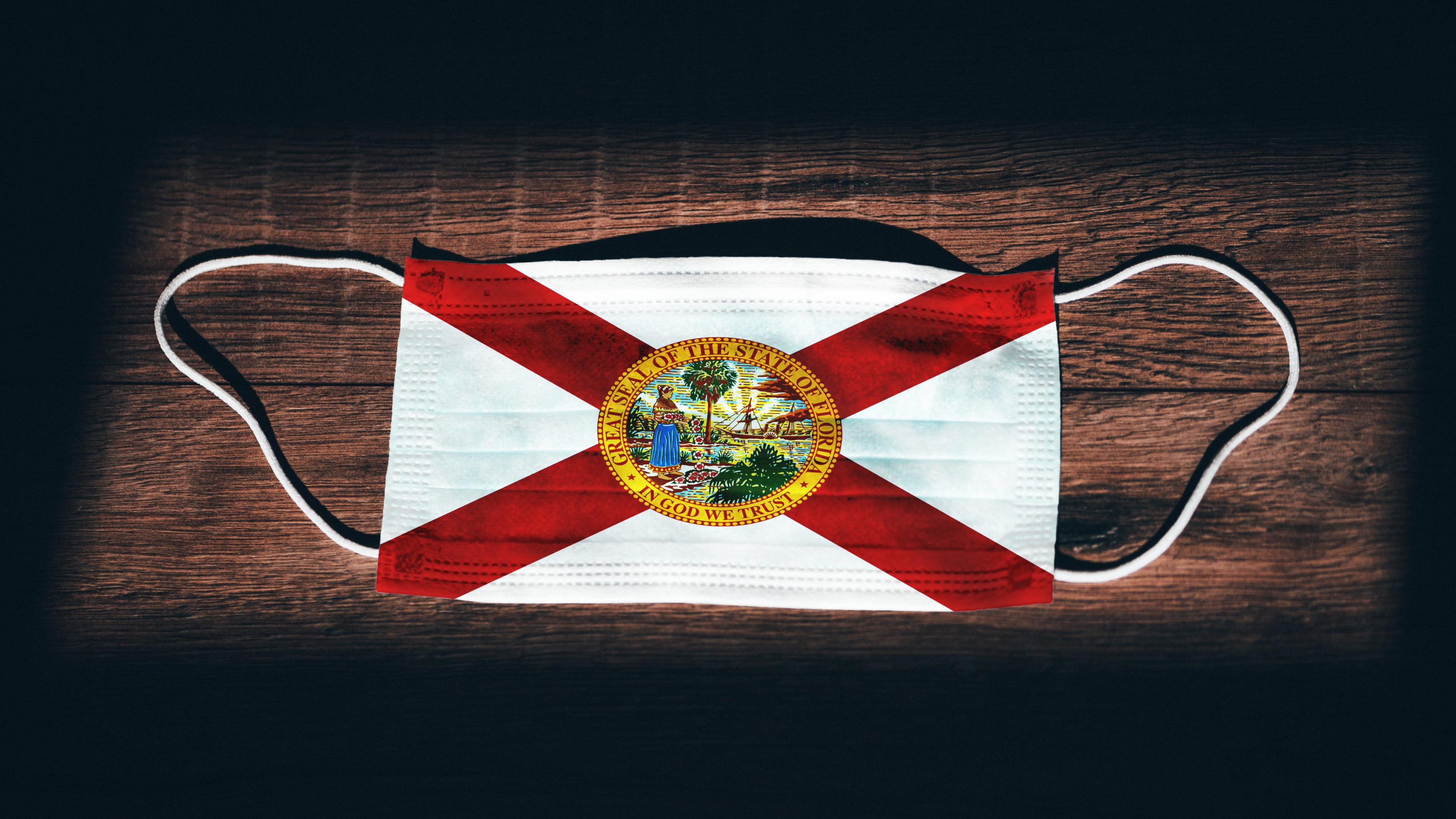 Florida Flag. Coronavirus Covid 19 in U.S. State. Medical mask isolate on a black background. Face and mouth masks for protection against airborne infections in USA, America