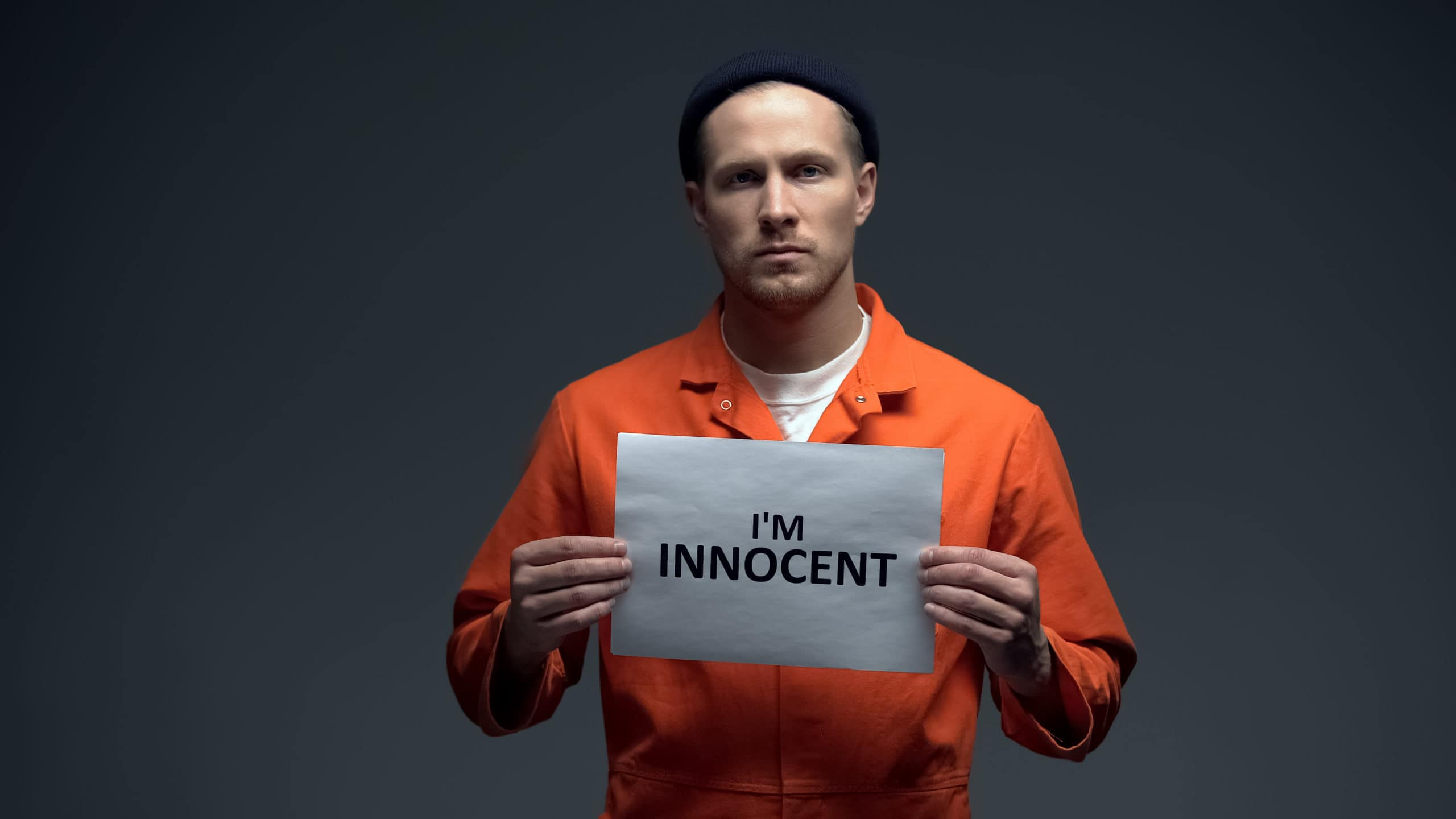 European imprisoned male holding I am innocent sign in cell, asking for justice