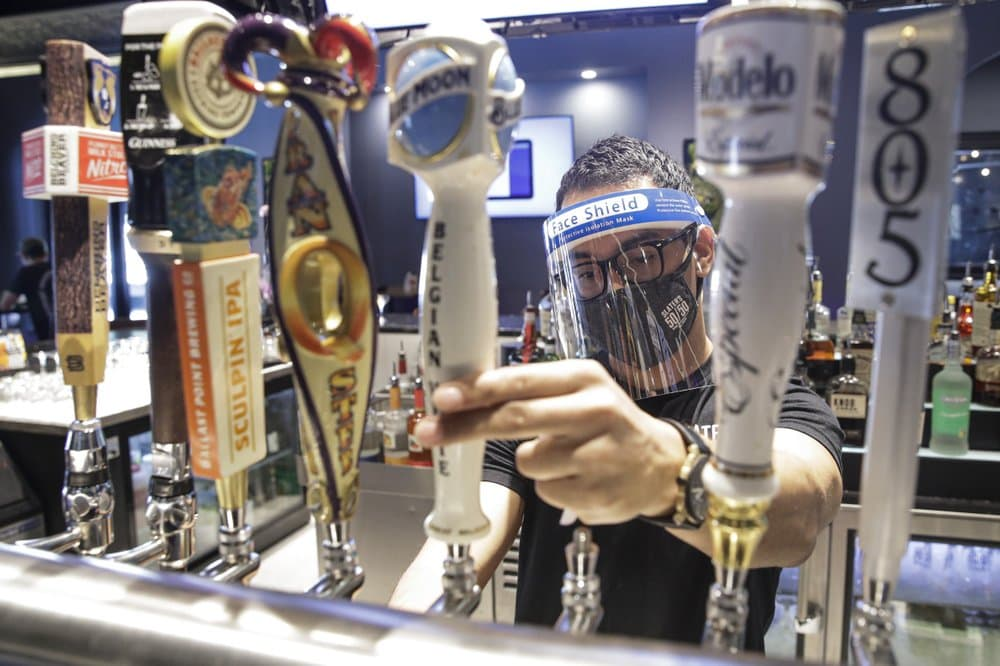 A-bartender-pours-a-beer-while-wearing-a-mask-and-face-shield-amid-the-coronavirus-pandemic-at-Slaters-in-Santa-Clarita-Calif.-California.jpeg