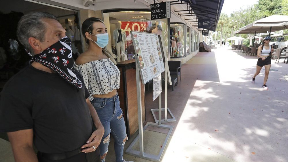 Restaurant workers Alvyn Lopez, left, and Maria Lindo watch for customers as they stand outside Aura at Books & Books, Monday, July 6, 2020, on Miami Beach, Florida's famed Lincoln Road. In Miami-Dade County, population 2.7 million, Mayor Carlos Gimenez ordered the closing of restaurants and certain other indoor places, including vacation rentals, seven weeks after they were allowed to reopen. Beaches will reopen on Tuesday after being closed over the weekend. (AP Photo/Wilfredo Lee)