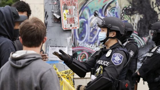 """A police officer engages with a protester Wednesday, July 1, 2020, in Seattle, where streets had been blocked off in an area demonstrators had occupied for weeks. Seattle police showed up in force earlier in the day at the """"occupied"""" protest zone, tore down demonstrators' tents and used bicycles to herd the protesters after the mayor ordered the area cleared following two fatal shootings in less than two weeks. The """"Capitol Hill Occupied Protest"""" zone was set up near downtown following the death of George Floyd while in police custody in Minneapolis. (AP Photo/Elaine Thompson)"""