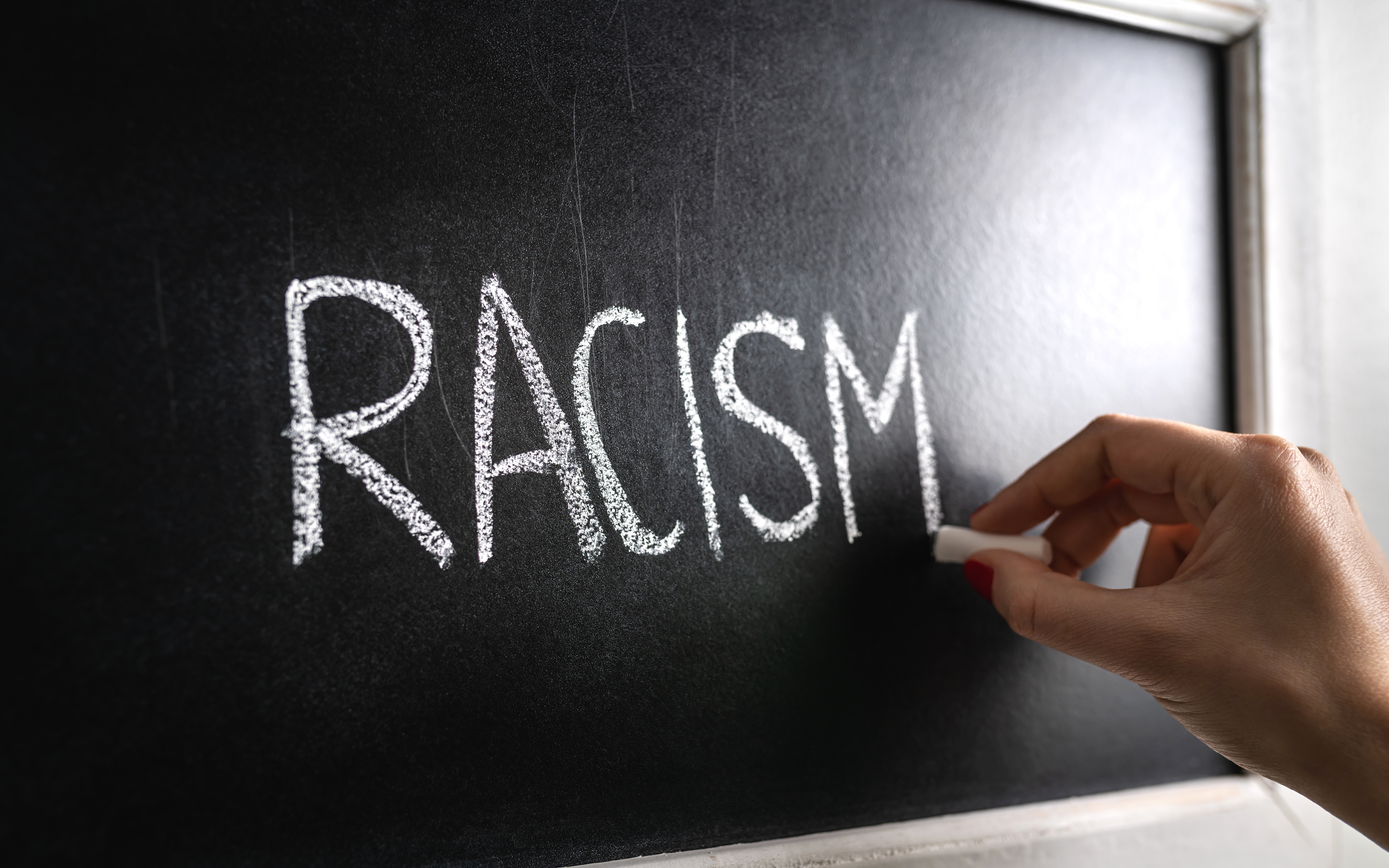 Hand writing the word racism on blackboard. Stop hate. Against prejudice and violence. Lecture about discrimination or stereotypes in school.