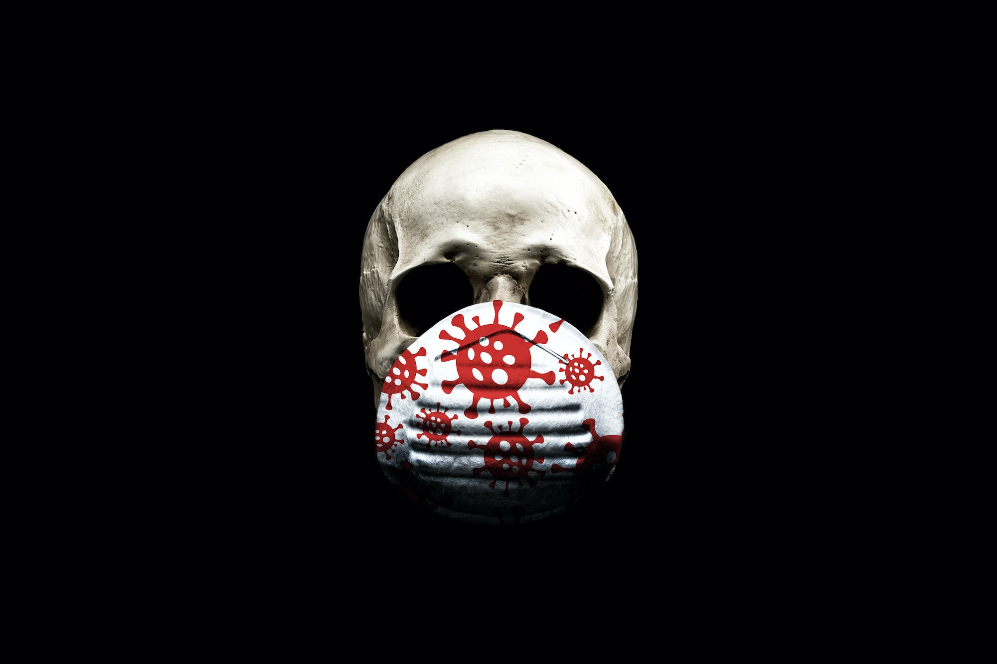 Skull in a medical mask isolated on black background . The concept of an epidemic. Coronavirus protection equipment.