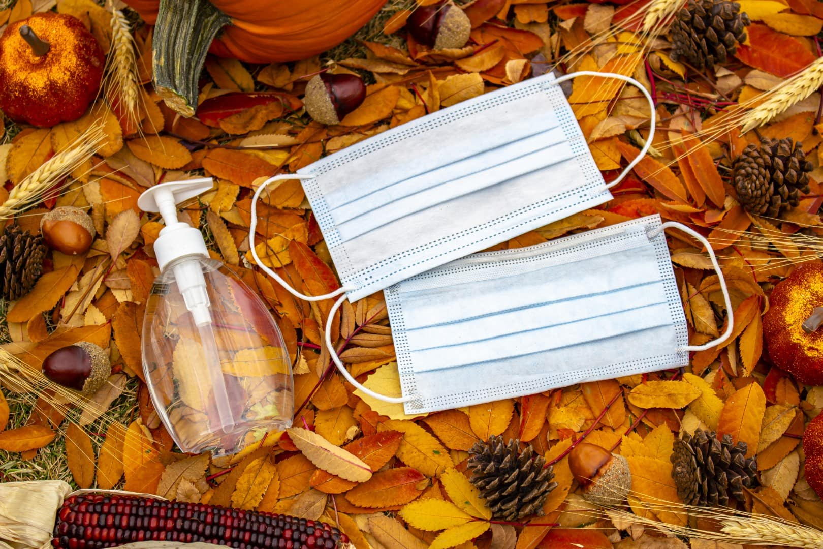 A bottle of a hand sanitizer and face mask on a halloween and thanksgiving background. Concept: Halloween and Thanksgiving during a pandemic, covid-19, coronavirus.