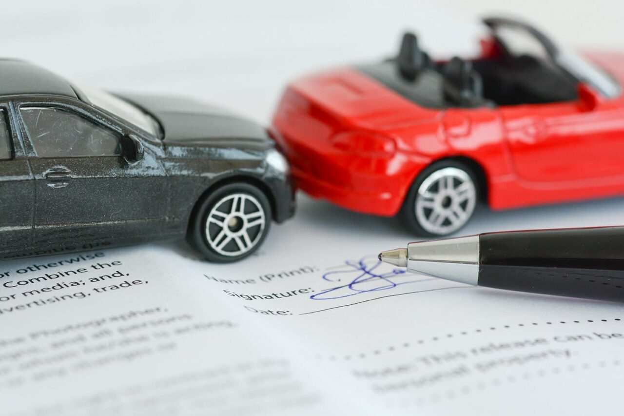 Insurance policy contract concept with toy model cars having a crash. Auto insurance, car insurance, PIP, no-fault.