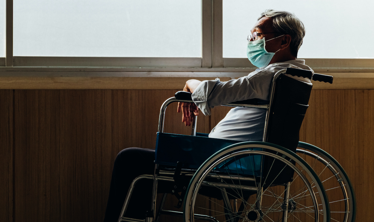 Retirement concept. Panoramic asian elderly man wear mask sitting in wheelchair while looking out the window in nursing home or hospital.