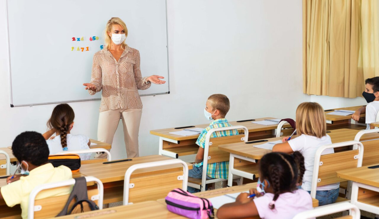 Female teacher in protective mask giving lesson to children