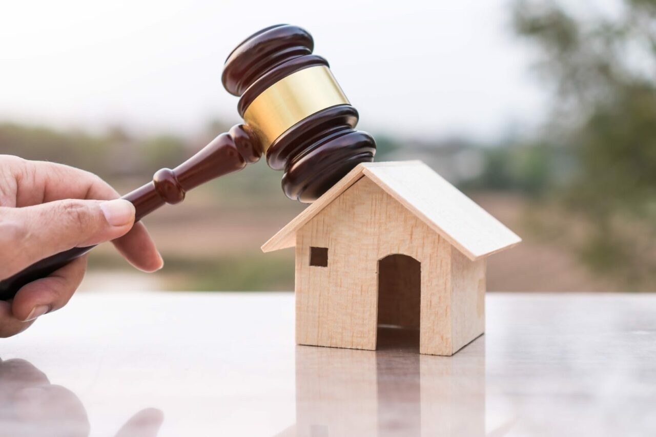 Judge gavel and house model property auction for real estate law concept. Lawyer hand holding gavel wooden knocking home ownership for buying selling or foreclosure on nature background.