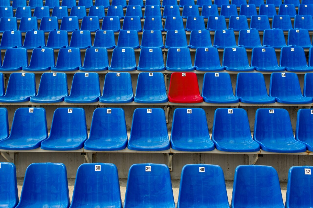 Dark blue rows of seats on the stadium. One red seat.