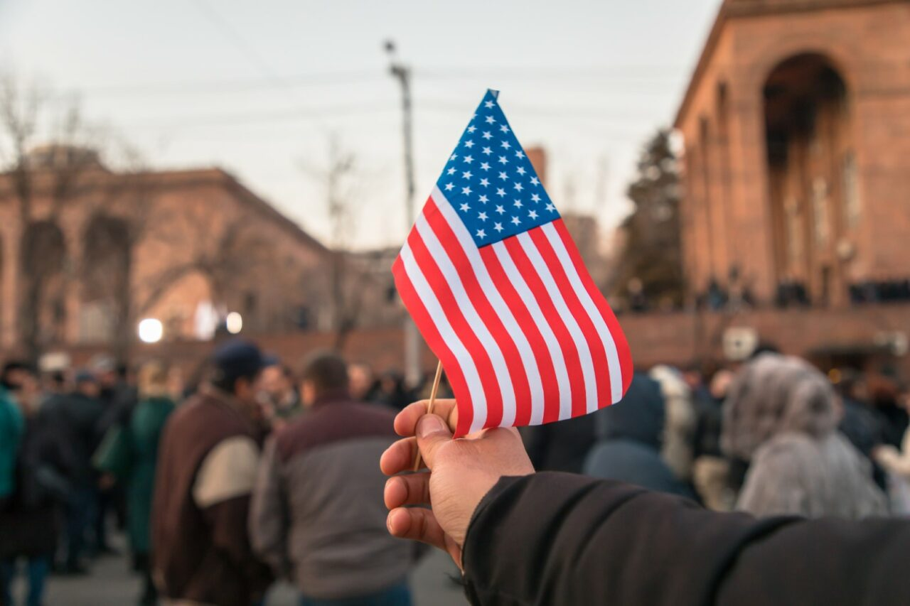 man holding American flag in street