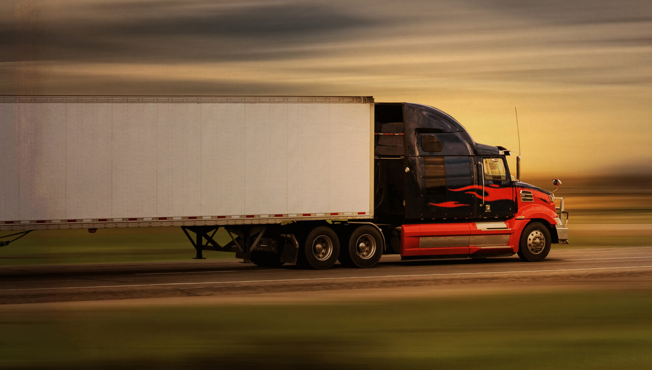 Bright modern big rig semi truck and trailer in motion on a high