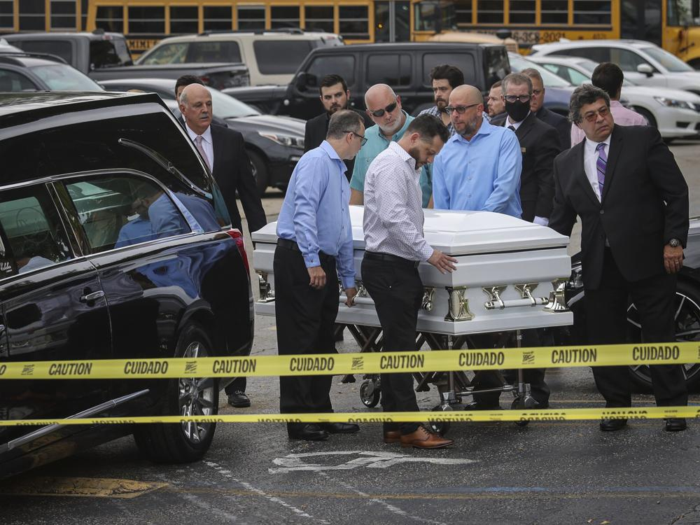 Pallbearers wheel a casket before a funeral service for Marcus Guara and his family at St. Joseph Catholic Church