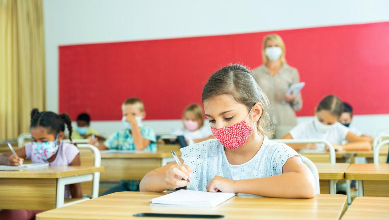 Diligent tween girl in protective mask studying in school